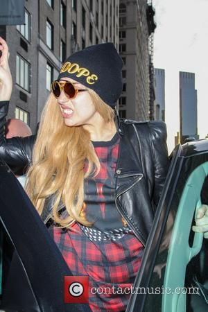 Lady Gaga - Lady Gaga dressed in a mini tartan patterned dress and black leather jacket topped by wearing a...