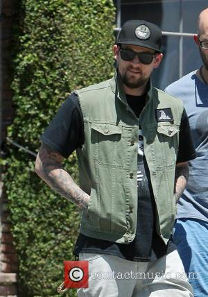 Joel Madden - Joel Madden wearing a 'Don't Tread on Me' vest jacket and camouflage smiley face baseball cap, meets...