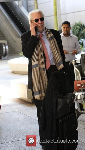 Donald Sutherland - Donald Sutherland chats on his mobile phone at Los Angeles International Airport (LAX) - Los Angeles, California,...