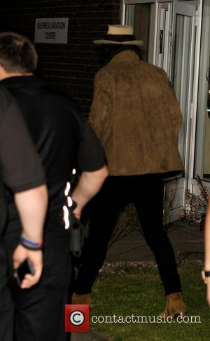 Harry Styles and One Direction - One Direction, surrounded by a heavy security team shielding the band from photographers, arrive...