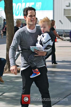Mike Comrie and Luca Comrie - Mike Comrie carries his son Luca Comrie who holds a toy hockey stick to...