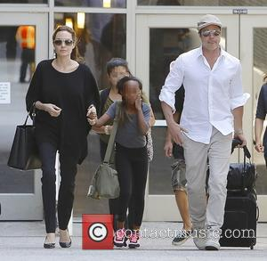 Angelina Jolie, Brad Pitt and Zahara Jolie-Pitt - Brad Pitt and Angelina Jolie arrive at Los Angeles International (LAX) airport...