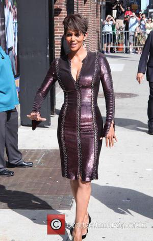 Halle Berry - Halle Berry, wearing a very tight corset style plum dress, arrives at the Late Show with David...