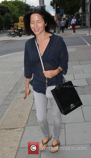 Andrea Corr - A fresh-faced Andrea Corr spotted wearing a see-through navy top, grey jeans, and Crocs sandals walking past...