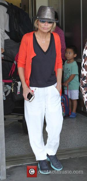 Kristin Chenoweth - Kristin Chenoweth at Los Angeles International Airport (LAX) wearing an orange cardigan, white trousers and a silver...