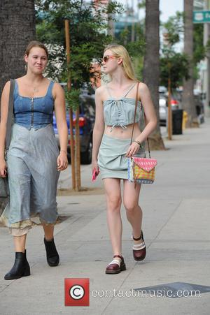 Elle Fanning - Elle Fanning carries a colorful bag while out and about having some laughs with a friend -...
