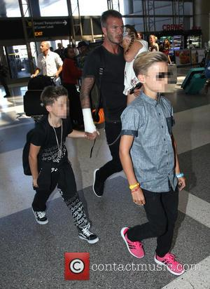 David Beckham, Harper Beckham, Cruz Beckham and Romeo Beckham - David Beckham arrives at Los Angeles International (LAX) airport with...