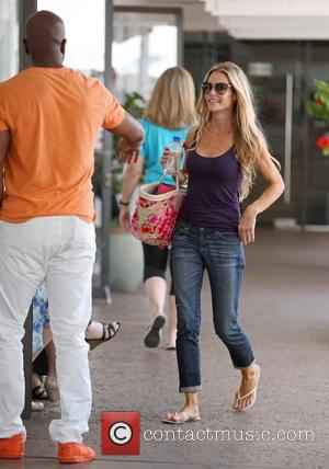 Denise Richards - Denise Richards looks casual in jeans, a tank top and a colorful bag on her visit to...