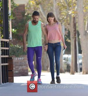 Shia LaBeouf and Mia Goth - Shia LeBeouf (sporting a light green vest and work-out gear) and his girlfriend, Mia...