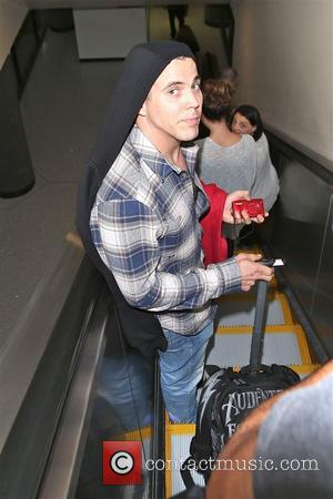 Jackass stuntman Steve-O pictured at L.A International Airport wearing a blue chequered shirt with jeans and a black hoody -...