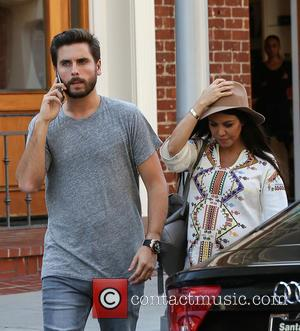 Scott Disick and Kourtney Kardashian - Scott Disick talks on his iPhone 6 as he and pregnant partner, Kourtney Kardashian...