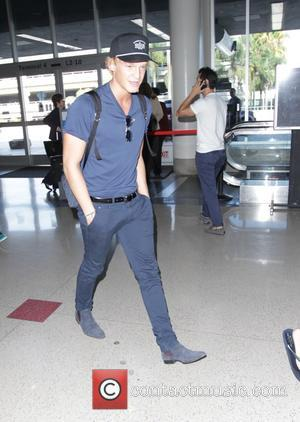 Cody Simpson - Australian pop singer, Cody Simpson dressed in blue, walks with his hands in his pockets as he...