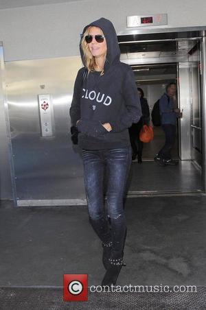 Heidi Klum - Heidi Klum arriving at Los Angeles International Airport wearing sunglasses and a hoodie with the word 'Cloud'...