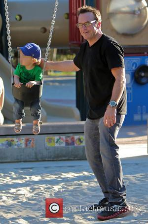 Tom Arnold and Jax Arnold - Tom Arnold pushes his son Jax on a swing during a day out at...