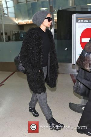 Nicole Richie - Nicole Richie arrives at Los Angeles International Airport (LAX) wearing Chanel sneakers and a very furry black...
