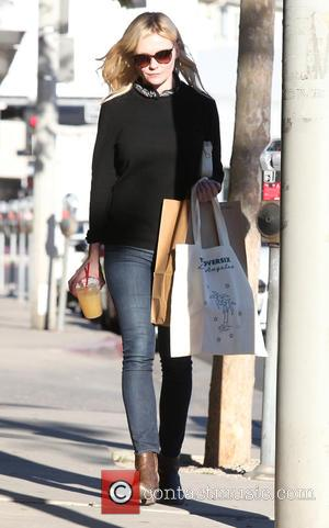Kirsten Dunst - Kirsten Dunst wearing a black top with skinny jeans and brown ankle boots out and about running...