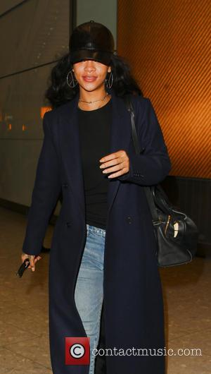 Rihanna - Rihanna arrives at London Heathrow wearing a full length winter coat and fur boots - London, United Kingdom...