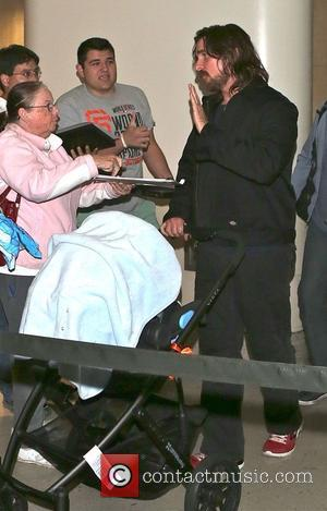 Christian Bale - A tired-looking Christian Bale arrives at LAX airport pushing his new baby boy in a pushchair with...