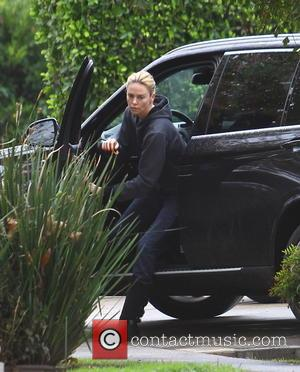 American Hollywood actress Charlize Theron was spotted as she dashed out from her black BMW SUV car wearing an all...
