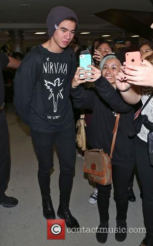 Australian pop band 5 Seconds of Summer were accosted by fans as they arrived at Los Angeles International airport in...