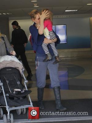 Uma Thurman and Luna Thurman-Busson - Uma Thurman arrives at Los Angeles International Airport (LAX) with her daughter, Luna, hiding...