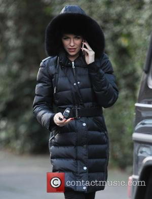 Abbey Clancy - Abbey Clancy chats on her mobile phone while out and about in Central London, wearing a warm...