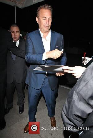 Kevin Costner - Kevin Costner signs autographs for waiting fans as he arrives back at his hotel after attending the...