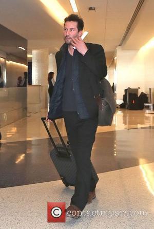 Keanu Reeves - Keanu Reeves departs from Los Angeles International Airport (LAX) carrying Louis Vuitton luggage - Los Angeles, California,...