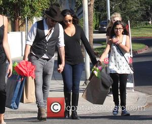 Zoe Saldana and Marco Perego - Zoe Saldana laden with shopping bags after visiting Landis' Labyrinth Toy Shop with husband...