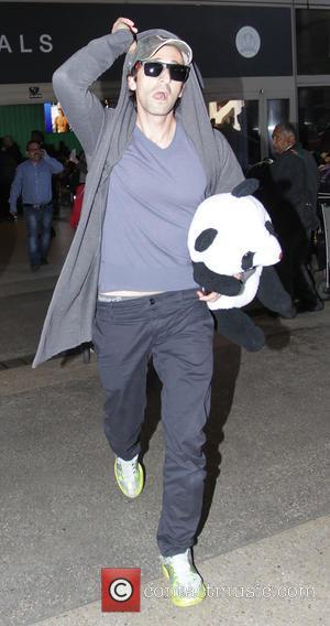 Adrien Brody - Adrien Brody arrives at Los Angeles International Airport (LAX) as he tries to hide in his hoodie,...