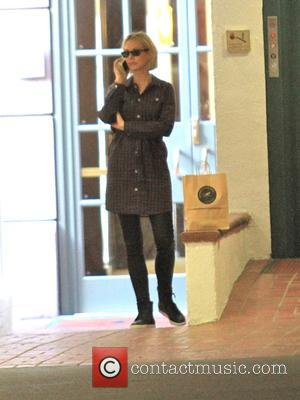 Jenna Elfman - Jenna Elfman makes a call on her cellphone and hangs around waiting after going shopping in Beverly...