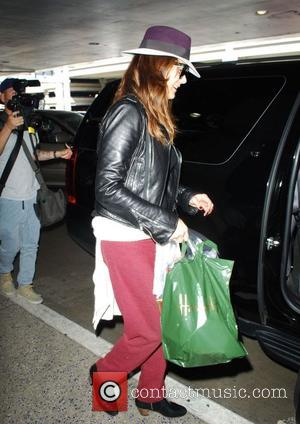 Kate Walsh - Kate Walsh arrives at LAX wearing a purple fedora hat at LAX - Los Angeles, California, United...