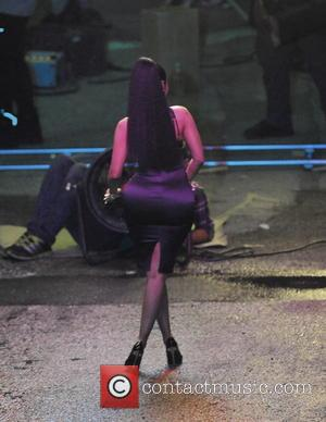 Nicki Minaj - Nicki Minaj struts her stuff and shows of her curves in a black tight dress for her...