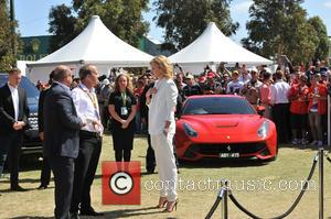 South African/American actress Charlize Theron was photographed wearing a white trouser suit as she attended the 2015 Australian Formula One...