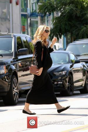 Molly Sims - Pregnant Molly Sims showing her baby bump in a black maxi dress crosses a busy street while...