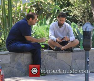 Tobey MaGuire - Bearded Tobey MaGuire sits crossed legged while chatting to a friend in Hollywood - Hollywood, California, United...
