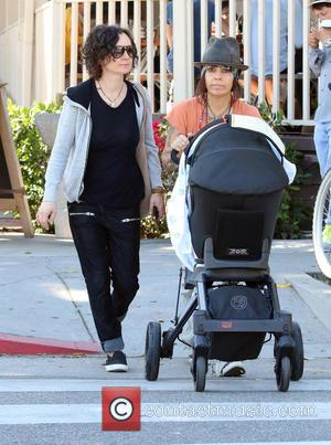 Sara Gilbert and Linda Perry - Sara Gilbert and wife Linda Perry take their newborn son Rhodes on a sunny...