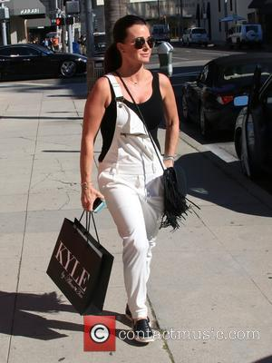 Kyle Richards - Kyle Richards wearing white dungarees and a black handbag with tassels, leaves Kyle by Alene Too on...