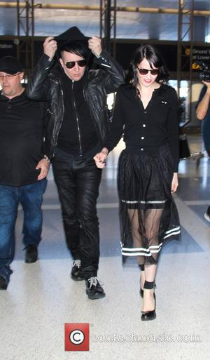 Marilyn Manson and Lindsay Ulrich - Make up free Marilyn Manson arrives at Los Angeles International Airport (LAX) to catch...