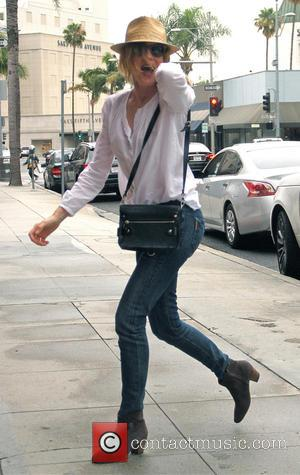 Rene Russo - Rene Russo wearing a straw hat, tight jeans ans brown suede boots goes to an office in...