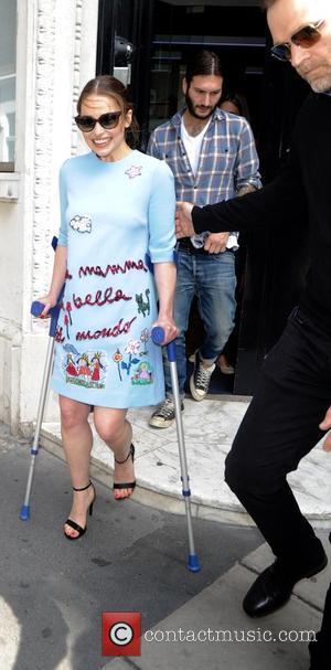 Emilia Clarke - Emilia Clarke seen walking on crutches as she leaves Magic Radio - London, United Kingdom - Thursday...