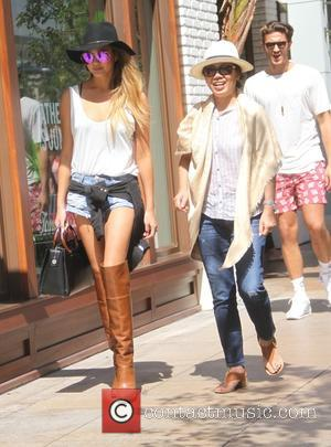 Chrissy Teigen and Vilailuck Teigen - Chrissy Teigen wearing purple mirrored sunglasses, thigh length boots and a wide brimmed hat,...