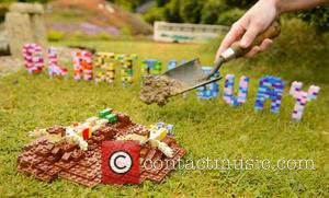 Pictured: Model maker Hannah Reed places real Worthy Farm mud in Glastonbury festival scene at the LEGOLAND Windsor Resort at...