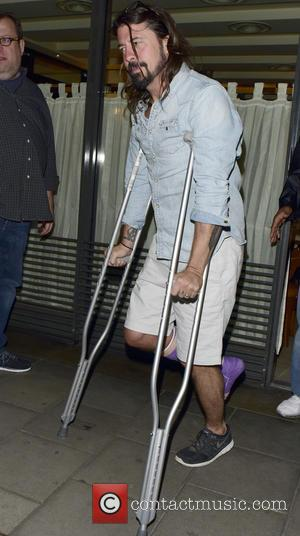 Dave Grohl and David Grohl - Dave Grohl leaving C London restaurant on his crutches with a purple cast on...