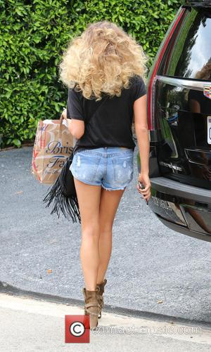 Chrissy Teigen - Chrissy Teigen with a new hair style arriving home in Beverly Hills wearing daisy dukes showing off...