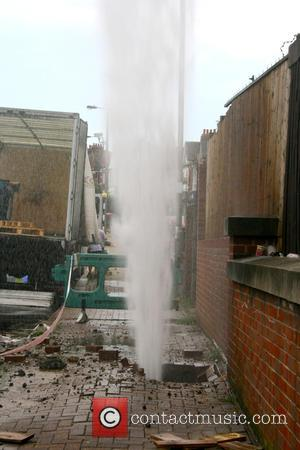Atmosphere - A burst water main sends water 5 stories high in Mitcham Lane, Tooting, South London, on the hottest...