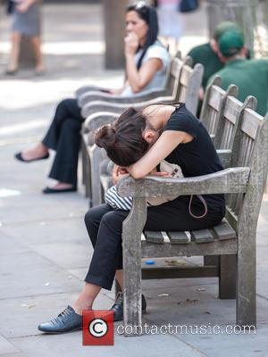 Atmosphere - As the sun beats down, a woman falls asleep on a bench in the City of London near...