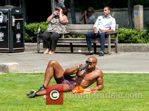 Atmosphere - Tourists and city workings sunbathing during their lunch breaks outside St Paul's Cathedral at St Paul's Cathedral -...
