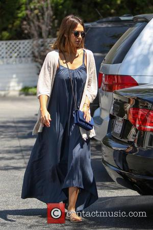 Jessica Alba - Jessica Alba pushing a trolley of groceries and bunches of white flowers in reusable shopping bags at...