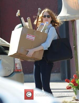Emma Stone - Emma Stone has her hands full with a box of music and office supplies on the set...
